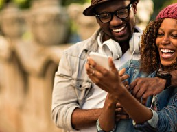 A Black couple laughs while seeing something funny on a phone.