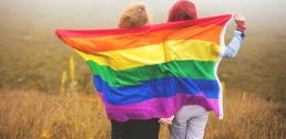 Two girls hold a rainbow flag while holding hands.