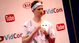 Young adult with headband and wristbands in front of a YouTube and VidCon backdrop.