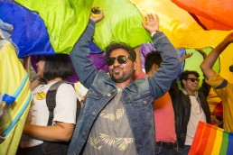 A man throws his hands in the air under a rainbow flag.